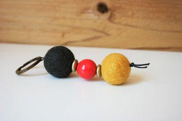Schlüsselanhänger mit Filz- und Holzperle, bzw. -linsen in den Farben der Deutschland-Flagge. Aufgefädelt auf eine schwarze Kordel. Optimal zur Fussball-EM in Frankreich. Dieser Schlüsselanhänger hat eine Länge von ca. 10 cm. Gerne kann ich auch einen Schlüsselanhänger nach deinen Vorstellungen herstellen.