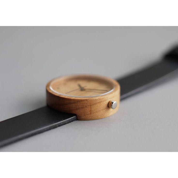 Cette montre en bois de cerise et cuir noir a été imaginée par la jeune marque…