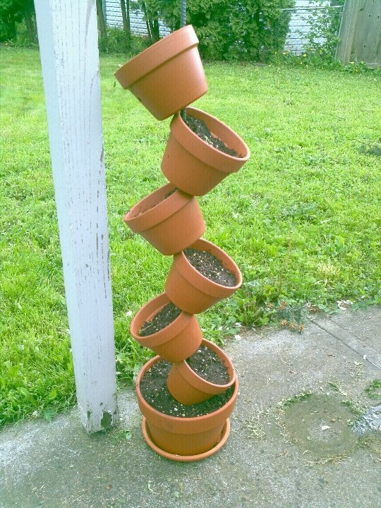 TILTED POT HERB GARDEN!    - 3/8 inch rebar (4 ft for this size)  - 2 pieces of 1 1/2 inch PVC pipe cut to fit criss cross in the bottom of the large pot (angle ends for best fit)  - as many pots as you want - large on bottom  - criss cross PVC pipe in bottom of large pot then drill a hole straight through both pieces in the center...rebar should go through both pieces and into the hole on bottom of pot  - suggest you fill smaller pots with dirt before you thread onto rebar
