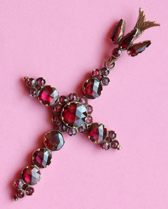 An 18 carat gold cross set with foiled faceted garnets suspended from a bird, Perpignan, circa 1830