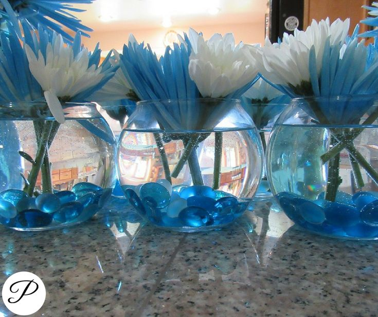 whale themed baby shower: we used small glass vases with blue stones and white and blue flowers for the table center pieces