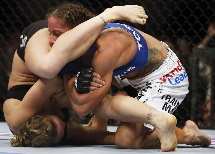 Ronda Rousey, left, tries to pull an armbar on Liz Carmouche during their UFC 157 womens bantamweight championship mixed martial arts match in Anaheim, Calif., Saturday, Feb. 23, 2013. Rousey won the first women's bout in UFC history, forcing Carmouche to tap out in the first round.