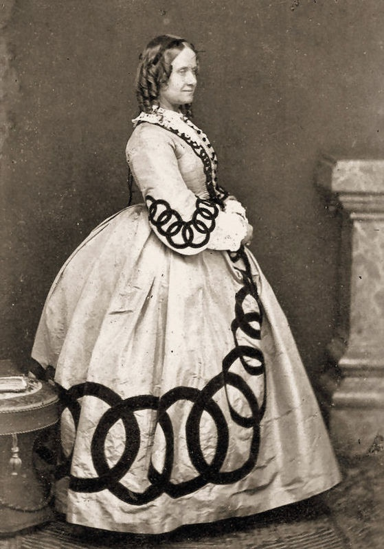 1860's Dress with dark intersecting rings as trim on the skirt & sleeves; photo