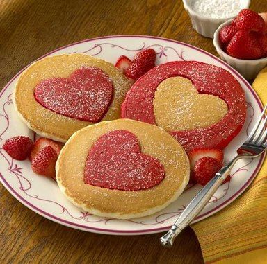 Prepare pancake mix, divide batter evenly into two medium-size bowls. Set one bowl aside.  Stir red food coloring into second bowl until batter turns deep pink color.  When pancakes are finished, place on wire cooling rack for two minutes. Transfer to cutting board.  Cut a heart out of the center of each pancake using a two-inch heart-shaped cookie cutter.  Place a red mini-pancake heart in the center of each white pancake and a white mini-pancake heart in the center of each red pancake.