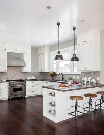 Contemporary kitchen features a beadboard ceiling over a white shaker cabinets adorned with oil rubbed bronze hardware and a gray quartz countertops, Caesarstone Lagos Azul, and a gray mosaic tile backsplash. A pair of industrial pendants hang over a kitchen peninsula fitted with end shelves lined with backless wood and iron counter stools.