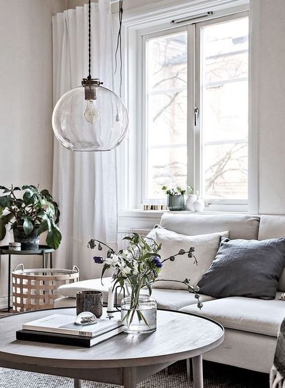 White living room couch with clear glass globe pendant