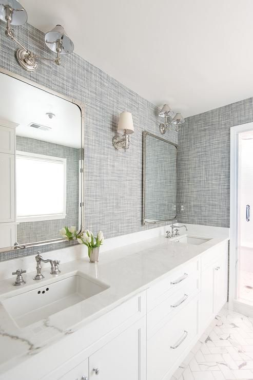 Beautiful white and gray bathroom is clad in gray textured wallpaper accenting marble herringbone tile floors framing a white dual vanity fitted with polished nickel hardware and a white marble countertop holding two sinks with vintage cross handle faucets beneath Restoration Hardware Industrial Rivet Flat Mirrors fixed beneath Ralph Lauren Anette Two Light Sconces and flanking a Jonathan Sconce.