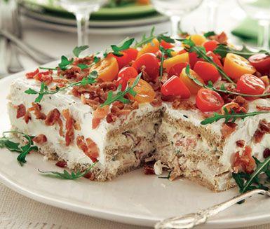Mumsig klassiker med bacon, kyckling och majonnäs – nu som smörgåstårta. Låt gärna stå i kylen över natten. Garnera med rucola och tomater strax före servering.