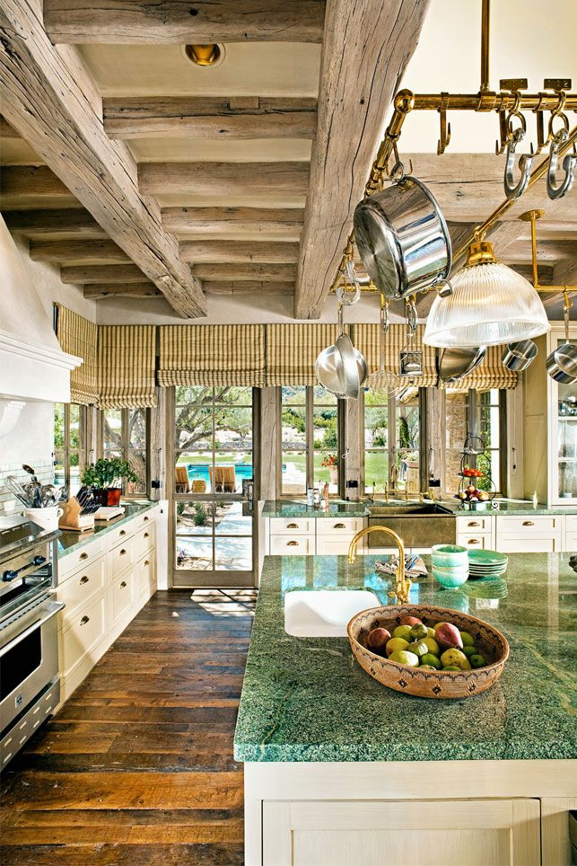 love the rustic beams and great way to save space  in the kitchen by hanging the pots .