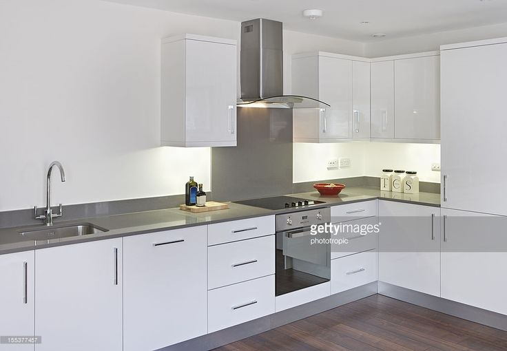 a modern white kitchen in a new apartment with integrated hob, oven and extractor fan. The cupboard doors are finished in white with stainless steel handles. This is not an expensive new home but nicely finshed. Lightly dressed for the image.