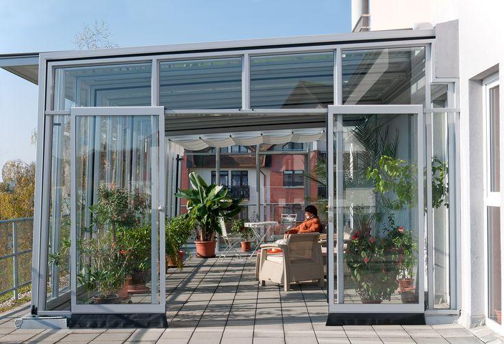 Boční pohled na otevřené dveře vedoucí do příjemného prostředí vytvořeného zastřešenou terasou systémem CORSO GLASS