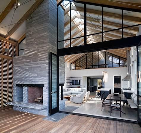 wonderful combination of natural light, wood beams, industrial glass, stone fire place by css architecture.
