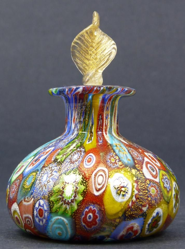 Murano art glass perfume bottle with stopper. Has a Millefiori like multicolor design with gold speckling throughout.