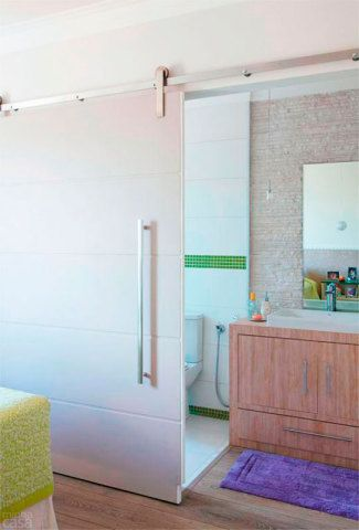 O espaço em que fica a bancada foi planejado para receber um minicloset, mas a arquiteta Josanda Ferreira rejeitou a ideia e estendeu o piso laminado do quarto até o lavatório. Uma porta de correr conecta o banheiro e o dormitório com muita classe e isola os ambientes quando desejado.