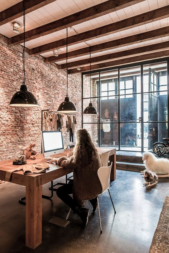 espace bureau dans une salle a manger, grande table de repas en bois, un ordinateur mac est posé dessus, trois suspensions noires industrielles au dessus de la table, ambiance lof, mur de briques rouges, grande verrière noire, poutres en bois apparentes au plafond