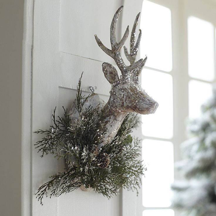 Our handcrafted reindeer head sparkles with glitter as does his faux evergreen and pinecone nest. This handsome deer will bring sophisticated holiday cheer to your mantel, entryway or dining room table.