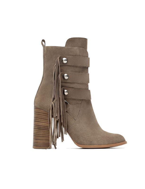El estilo setentero se adueña de estos botines de Zara, con efecto botones de casaca militar y flecos bohemios. Cuestan