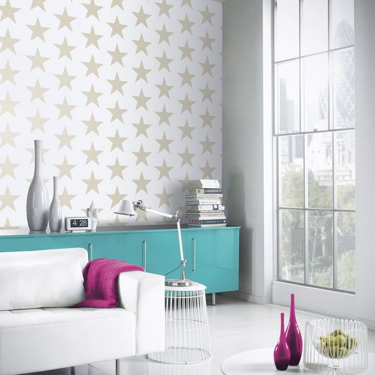 Arthouse Starry Night Wallpaper - Gold and White 891300  This fun Starry Night Wallpaper by Arthouse features a contemporary repeated star motif with a raised textured finish. The stars come in a pale gold tone with added glitter and metallic highlights on an off-white matte background. Easy to apply, this high quality wallpaper would look great as a feature wall or equally as good when used to decorate a whole room. A fun star patterned wallpaper Features glitter and metallic highlights…