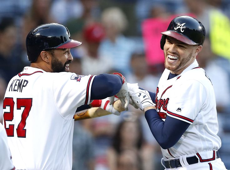 ATLANTA, GA - SEPTEMBER 13: First baseman Freddie Freeman #5 of the Atlanta Braves (right) is congratulated by left fielder Matt Kemp #27 after Freeman hit a 2-run home run in the first inning during the game against the Miami Marlins at Turner Field on September 13, 2016 in Atlanta, Georgia. (Photo by Mike Zarrilli/Getty Images).