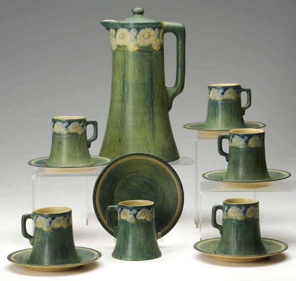 """NEWCOMB COLLEGE: Transitional chocolate set by Ora Reams, complete with six cups and saucers, carved with yellow daisies. Small chip to edge of two saucers, tight opposing lines to one cup. Chocolate pot marked NC/JM/B/ORA REAMS 1913/FH2. Pot: 10 1/2"""" x 6"""""""