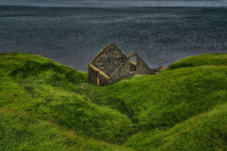 The ruins of a house by the shores of the sea on the island of Eysturoy in the Faroe Islands.