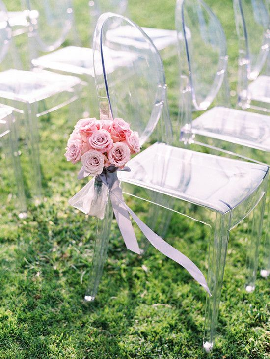 crystal clear wedding chairs accented with aisle flower arrangements