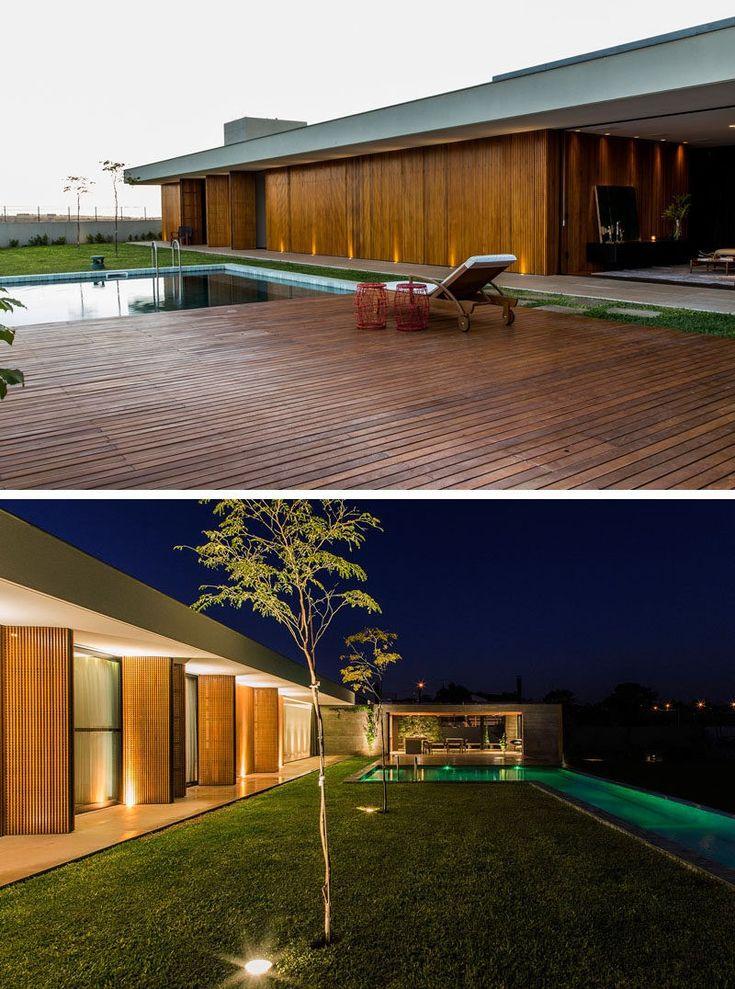 In der Nacht sind Bäume, Schwimmbad und äußere dieses Hause beleuchtet.