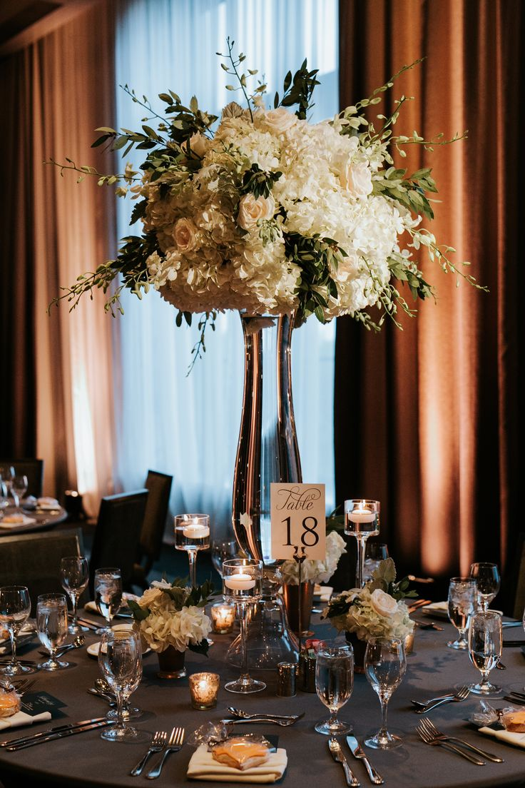 Tall gold vases topped with full and naturally textured sprays of cream hydrangeas, ivory polo roses, white/green parrot tulips, sprawling white dendrobium orchids and nagi foliage to pull the arrangements out a bit to be a little more loose...STEMS Floral Design   Hotel Van Zandt   Clearly Classy Events   Stacey Conat Photography