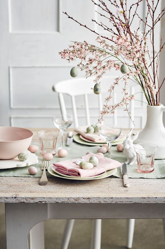 Easter Decoration, dining room table for the Holiday. Decorate with eggs, feathers and flowers with pink and green details.