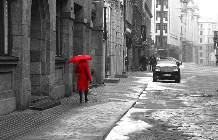 woman wearing red coat carrying red umbrella black