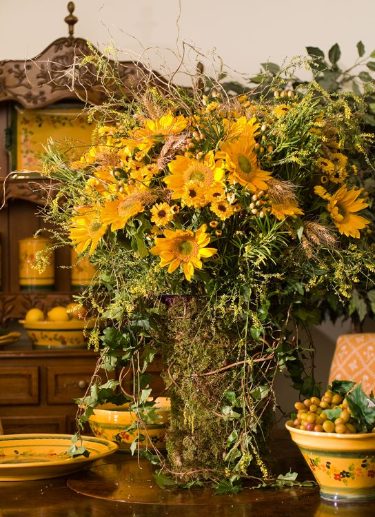 Bouquet Provencal, featuring sunflowers, wheat, and summer wildflowers in a moss and vine-wrapped vase, transports the viewer to the south of France.