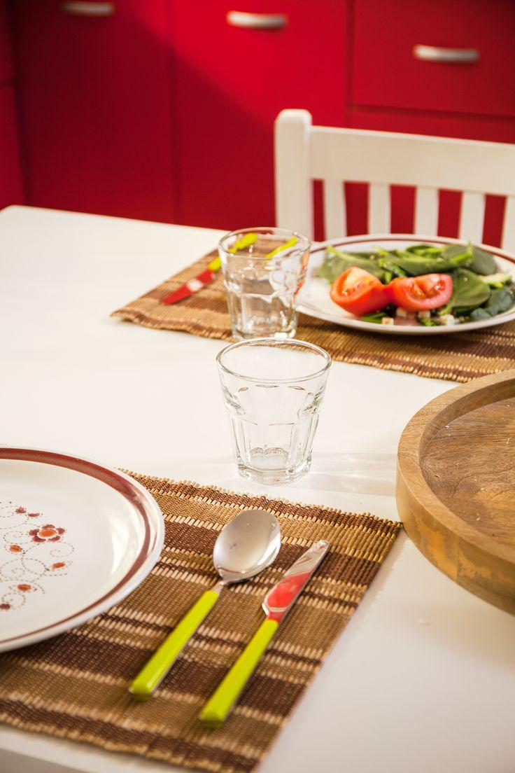 Incluye tonos rojos en la decoración de la mesa de cocina para complementar tu proyecto.