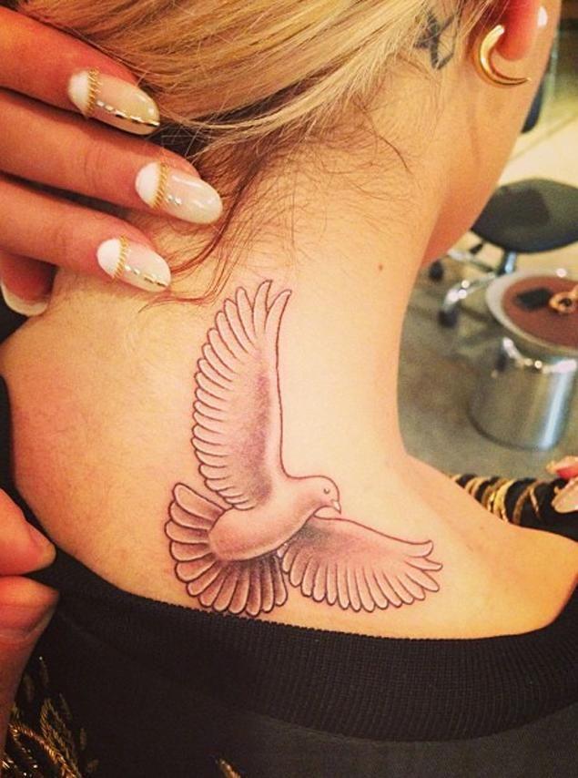 Rita Ora shows her new dove tattoo.