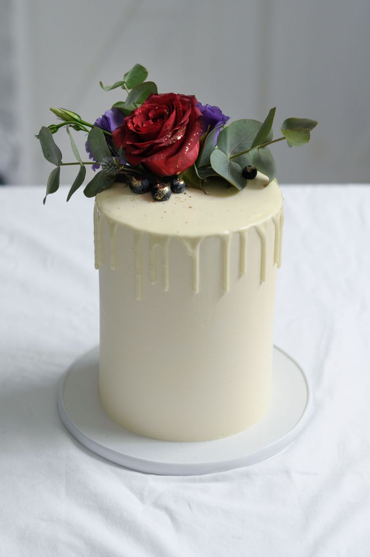White bridal cutting cake with fresh flowers by LionHeart