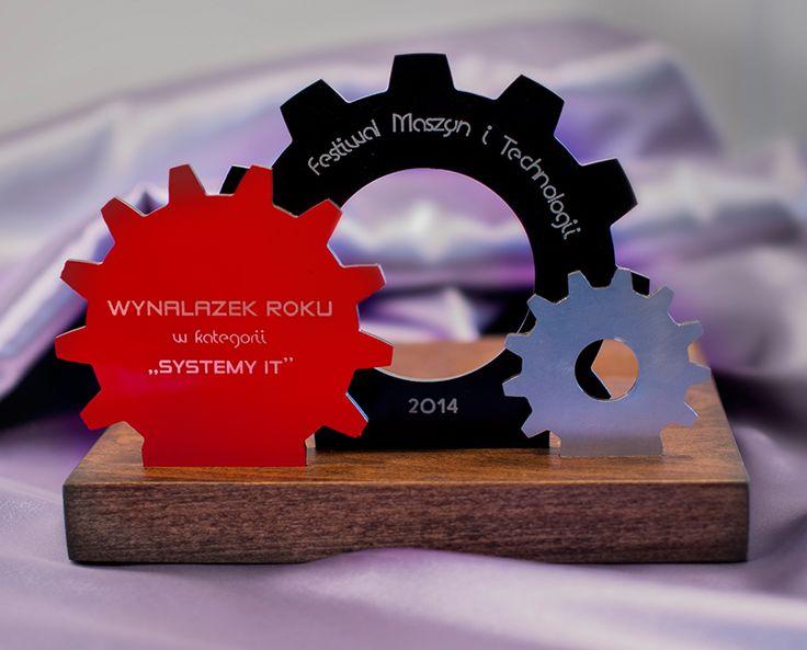 Statuetka na Festiwal Maszyn i Technologii w kształcie kół zrębatych.rożnych kształtach i wielkościach. Wykonana  z pozornie niepasujących elementów - drewna i dibondu.