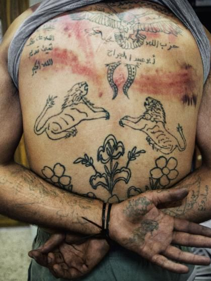 The back of Zakariyya Gazmouz, a suspected Shabiha prisoner, his body covered in pro-Assad tattoos that he later defaced with a razor. Marae, Syria, July 2012.