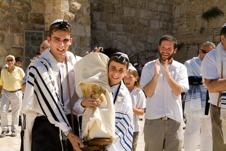 Israeli cultural identity. These boys are wearing traditional style of Jewish clothing and are carrying traditional scrolls. They are participating heavily in their culture.