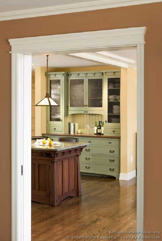 sage green painted kitchen cabinets with soft yellow walls;