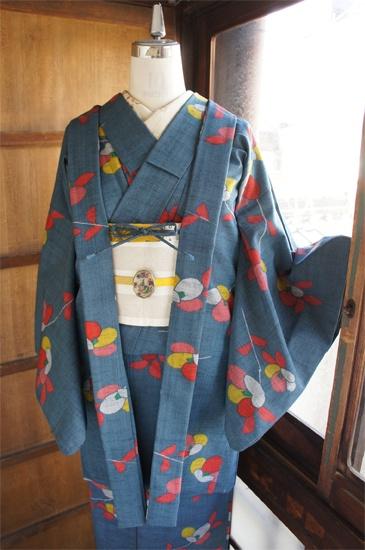 淡い青みがかかったグレーの地に、こっくりとしたピンク、黄色、赤、白、緑などの色合いも愛らしい椿模様が織り出されたウールのアンサンブル(着物と羽織のセット)です。