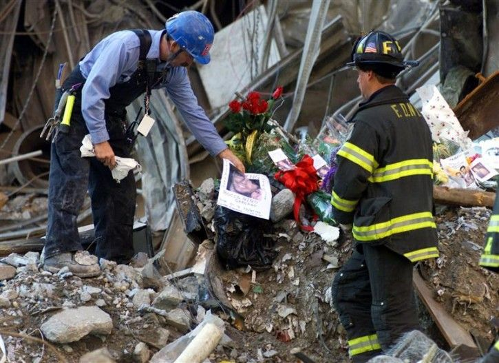 A New York City firefighter places a photograph on a pile of flowers and mementos from family members of the victims of the World Trade Center disaster amidst the wreckage at Ground Zero, following a memorial service for the victims of the September 11 attack at the site in New York, October 28, 2001.
