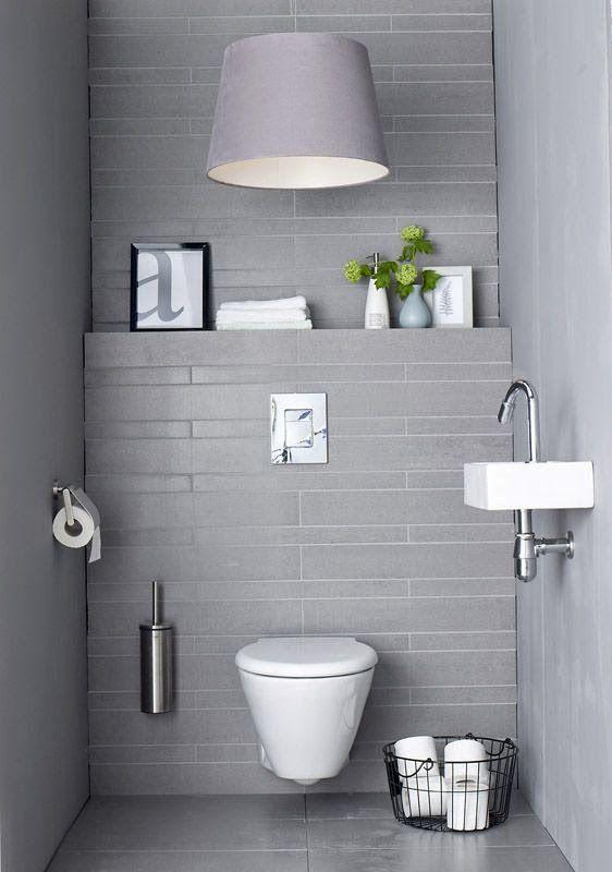 Grey, minimal tiled bathroom. Built in shelf to hold art!