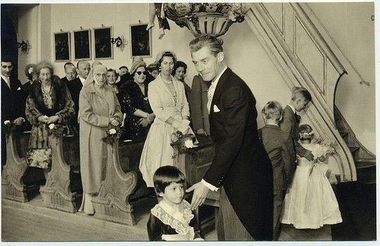 Prince Georg Wilhelm (George William) of Hanover (1915-2006), son of Ernst August, Duke of Brunswick and Princess Viktoria Luise of Prussia, seen here ushering a small page boy at a wedding. In the pew behind him is his wife, Princess Sophie of Greece (1914-2001) who was first married to Prince Christoph of Hesse-Cassel. Behind her is Princess Andrew of Greece (1885-1969), previously Princess Alice of Battenberg, mother of Sophie and also mother of Prince Philip, Duke of Edinburgh.