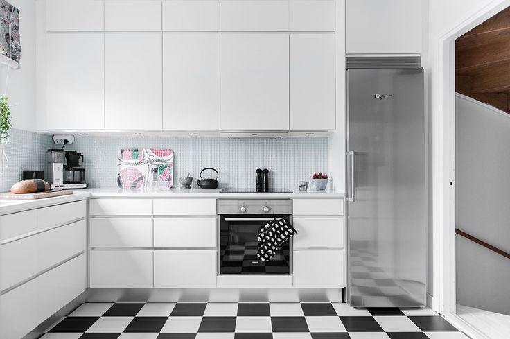 Skåpinredning i vitt från Ballingslöv. Bra arbetsytor på köksbänken. Ovan bänken sitter en glasmosaik som snyggt belyses av infällda spotlight under överskåpen.