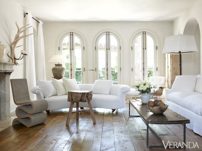 Modern neutrals dominate designer Pamela Pierce's French-style Houston home, like in this light-filled living room that mixes the old, the new, and the unexpected. Find the full tour here. Rolled-arm antique English sofa and 18th-c. iron candlestand floor lamp, W. Gardner, Ltd. Frank Gehry Wiggle Chair, Vitra. Tri-leg 19th-c. elm table, Area.