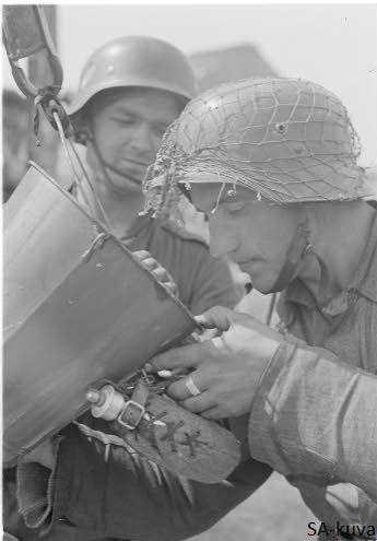 Finnish soldier fufilling his field water bottle during a break on Battle of Tali ihantala 1944.06.30
