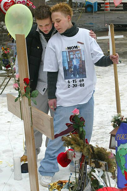 The T-shirt breaks my heart...Kayla Ayer, on left, 16, of Coventry, R.I., and best friend Nicole Lataille, 21, of West Warwick, pause in front of the cross they placed with a shovel in front Tina Ayers memorial at the scene of The Station nightclub fire. Kayla's mother Tina Ayer was one of 100 people who died at The Station nightclub fire...