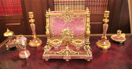 Fine Continental Louis XVI style gilt-bronze and rhodonite seven-piece desk set  probably russian or french  Comprising an inkstand, chamberstick, cassolette, bell, pair of candlesticks with ram's head mounts, and a document case with caryatids flanking the central panel opening to reveal interior compartments and a pink leather writing surface. (7).  H: 10 1/2, W: 14 1/2, D: 7 1/2 in.