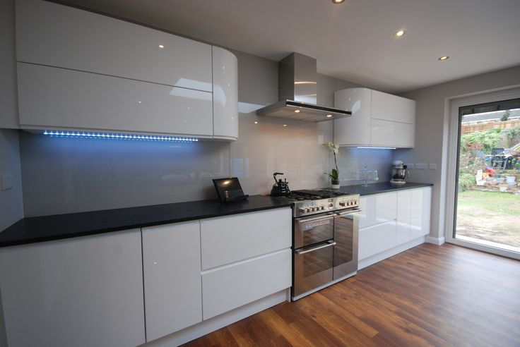 High Gloss White J-section kitchen with Black Granite Worktop by Saffron Interiors.  #white #gloss #kitchen #black #granite #island # grey # glass #lighting #modern #wood #floor