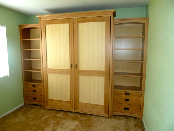 Two door craftsman murphy bed made of amber and blonde bamboo. Also with customized side bookshelves.