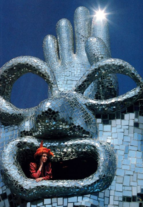 Artist Niki de Saint Phalle photographed in one of her sculptures by Franco Fontana for American Vogue, December 1987.